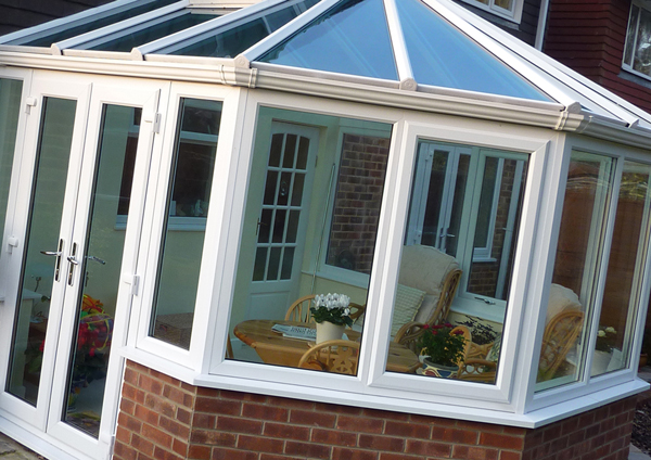 Image of a white, lantern-style upvc conservatory on brick plinth wall, with double doors