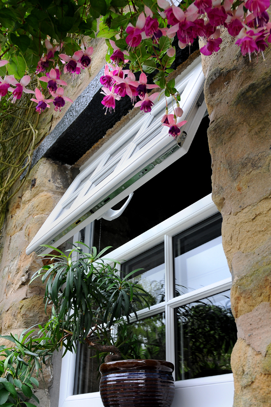 Image of a upvc double-glazed window, newly installed to a stone cottage and surrounded by trailing fuschia